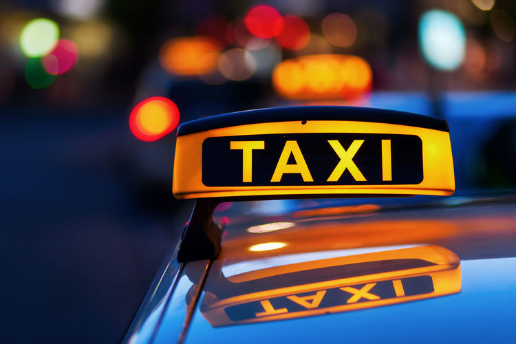 illuminated taxi sign on the roof of a taxi at night Car City City Life Close-up Focus On Foreground Illuminated Lights Neon Neon Sign Night Night Life Night Lights No People Outdoors Reflection Street Light Street Lights Taxi Taxi Sign Transportation