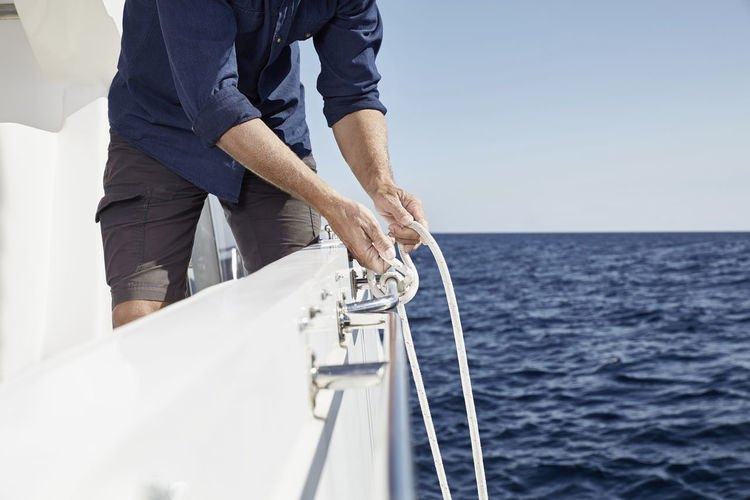 Low angle view of men sailing on sea against sky