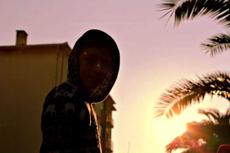 Low angle view of boy wearing hooded shirt during sunset