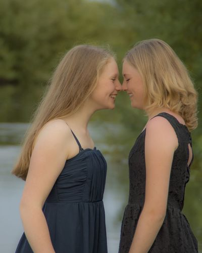 Side view of female friends rubbing noses while standing against lake