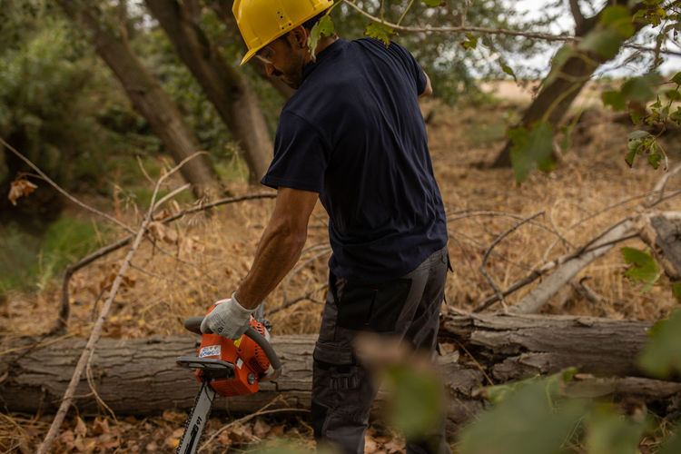 Man cutting wood with chain saw in forest