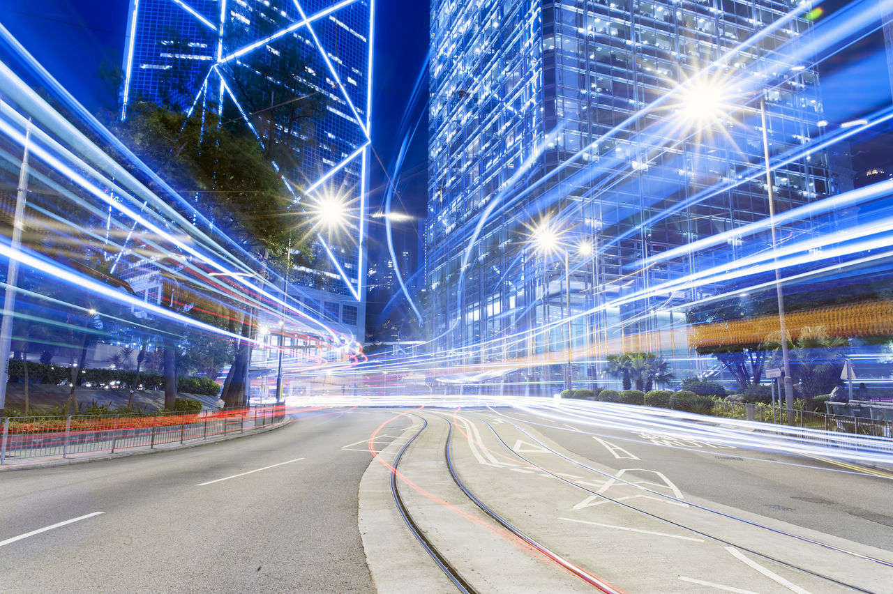 Light Trails On Street Against Illuminated Buildings In City