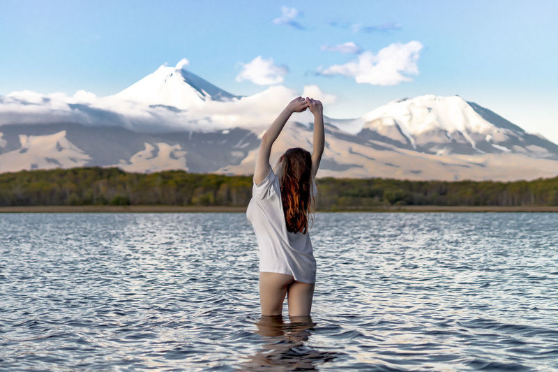 Rear view of woman with arms raised standing in lake against snowcapped mountains