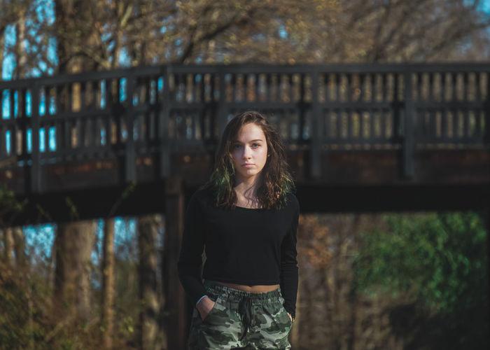 Portrait of girl standing against bridge in forest