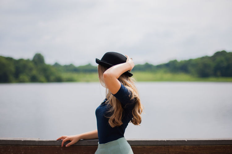 Woman wearing bowler hat standing by railing against lake