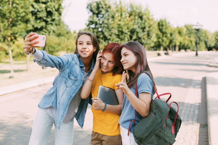 Three charming friends take selfies with their phone on the way to school. the concept of friendship