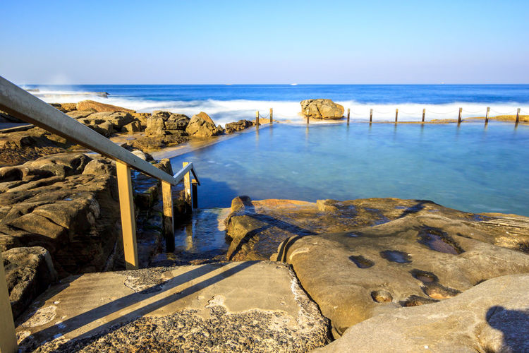 Slow down capture of the Mahon Rock Pool, with smooth waves and water. The railing leading in the pool is visible. Swimming Beauty In Nature Clear Sky Day Horizon Over Water Landscape Mahon Pool Nature No People Outdoors Pool Rock Pools Scenics Sea Sky Swimming Pool Tranquil Scene Tranquility Travel Destinations Water