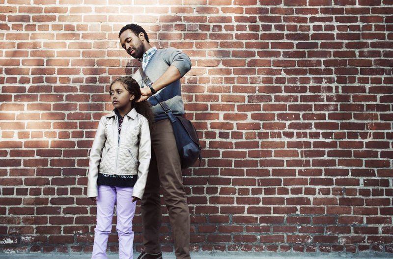 Father tying daughter's hair while standing against brick wall