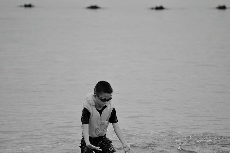 Boy wearing life jacket while playing on shore at beach