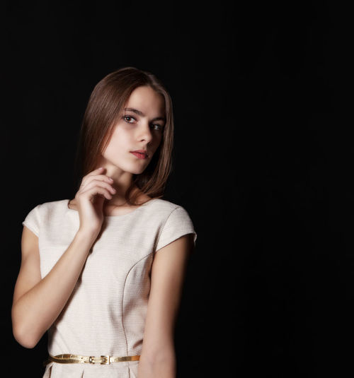Portrait Of Beautiful Young Woman Standing Against Black Background