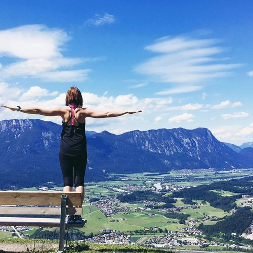 Rear view of woman standing on bench with arms outstretched by mountains against sky