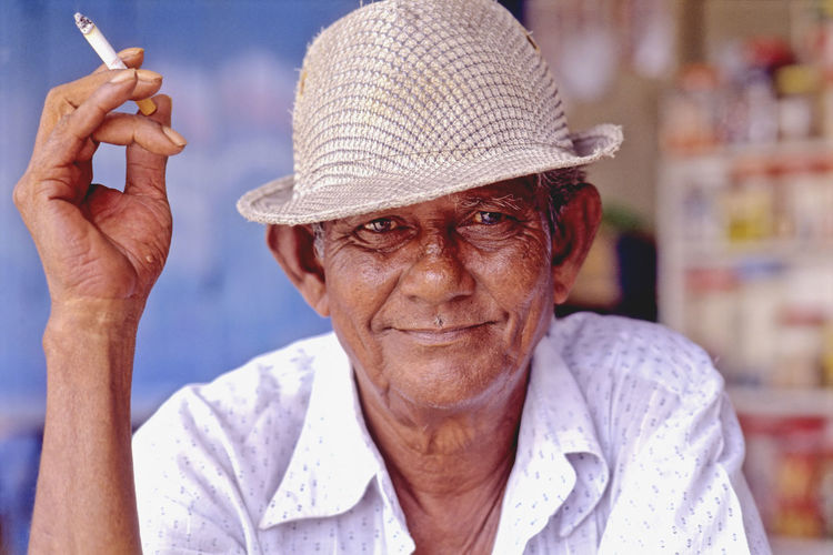 Asia, Malaysia, Malacca, Portuguese Settlement, Portrait of old man of Portuguese descent Cigarette  Color Image Hat History Horizontal Malacca Malaysia Man Portrait Portugese Descent Portugese Settlement Smoking Traditional