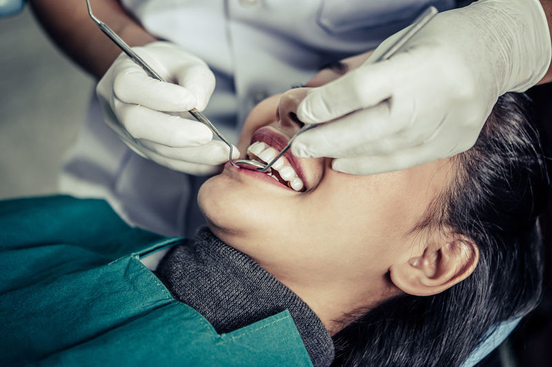 Midsection of dentist examining female patient