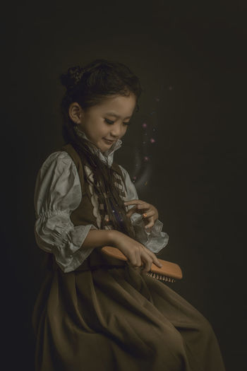 Girl combing hair while sitting against black background