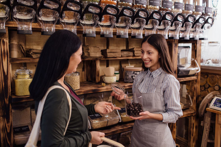Woman buying healthy chocolate in organic shop. Zero waste shopping. Zero Waste Plastic Free Package Shop Store Raw Food Food Refill Organic Shopping Business Homemade Horizontal Grocery Bulk Interior Container Dispenser Customer  Assistant Shopkeeper Two People Bio Eco