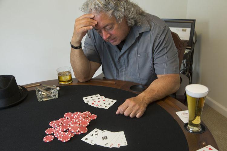 Man Playing Poker While Sitting At Table