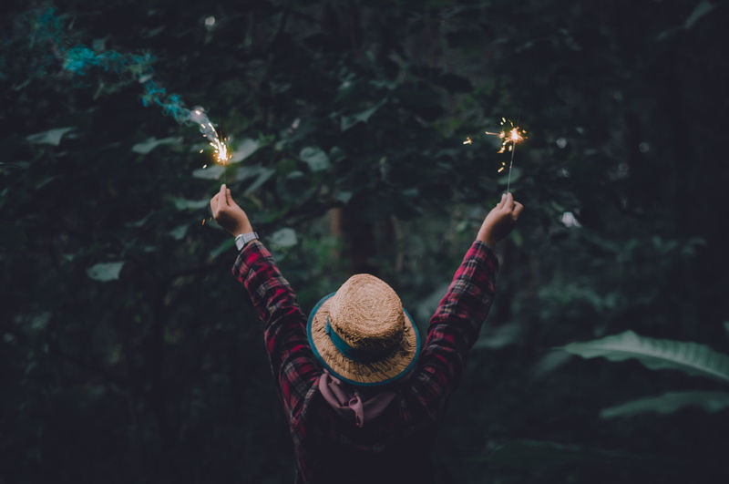 Rear view of woman wearing hat holding sparklers outdoors
