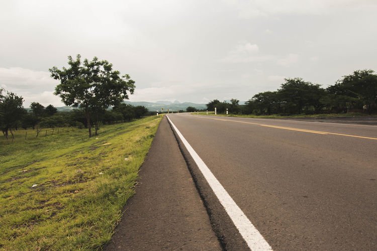 Cloud Cloud - Sky Country Road Countryside Day Diminishing Perspective Empty Empty Road Green Color Landscape Long Nature Non-urban Scene Outdoors Remote Road Road Marking Scenics Sky The Way Forward Tranquil Scene Tranquility Transportation Tree Vanishing Point