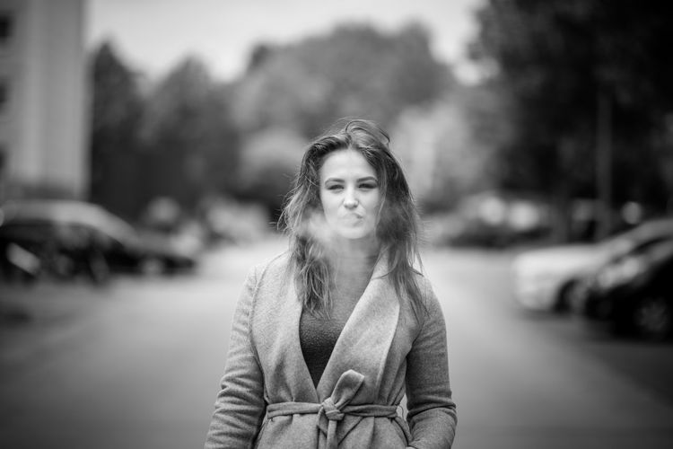 Portrait of woman exhaling smoke while standing on street in city