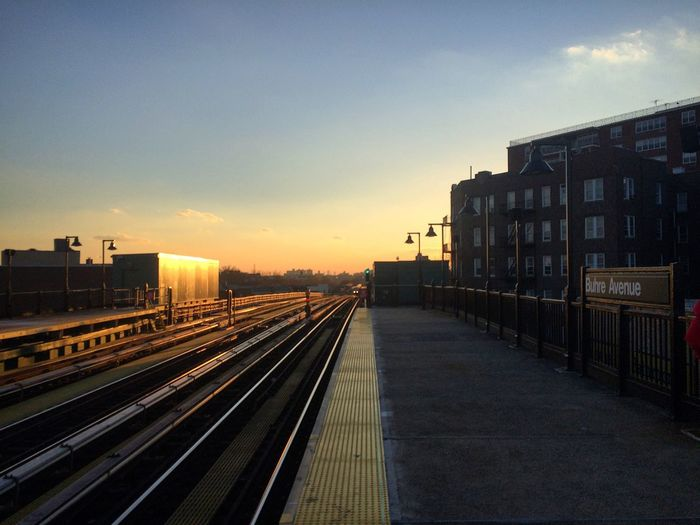 Railroad tracks amidst buildings in city against sky during sunset