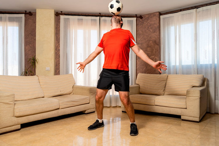 Rear view of man sitting on sofa at home
