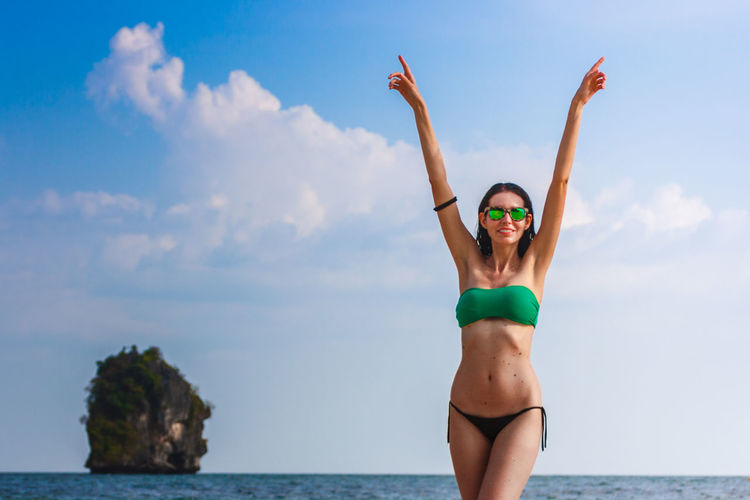 Portrait of woman wearing bikini with arms raised at beach against sky