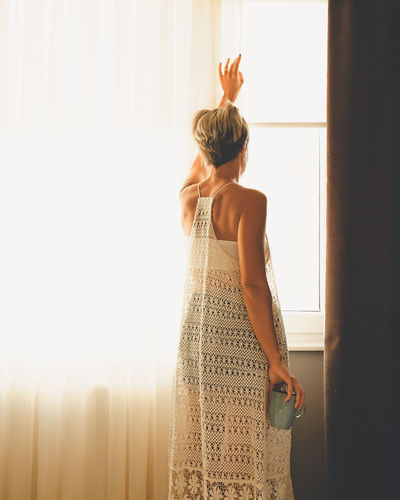 Adult woman looking out of the window. view from the back with cup in her hand.