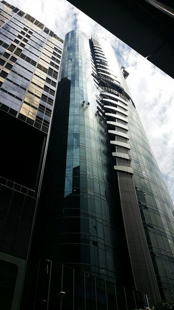 These guys were peeling the covering off the building. Risky Business Building Architecture Singapore