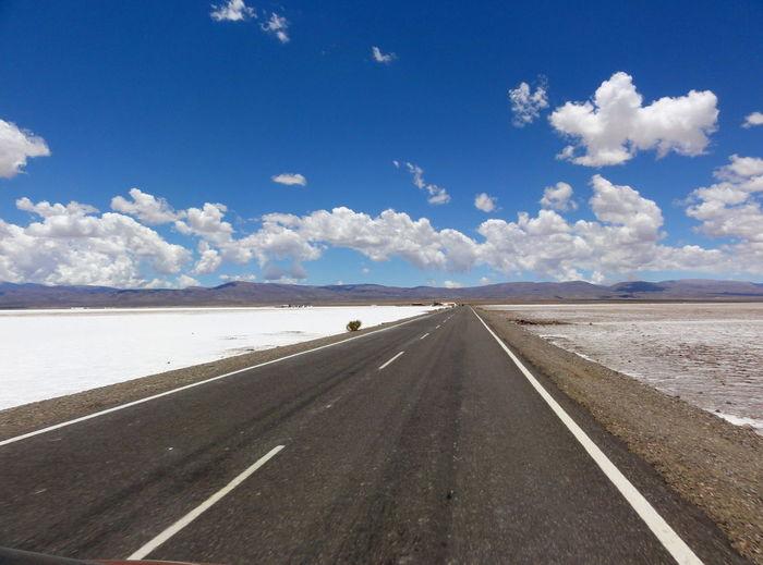 Empty road by salt flat against sky