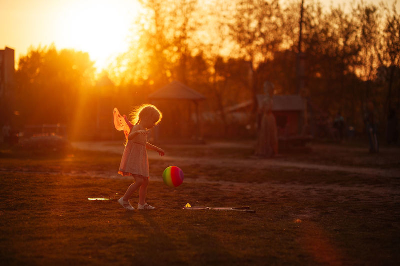 A girl in butterfly krulya plays with a ball on the field in the summer at the golden hour