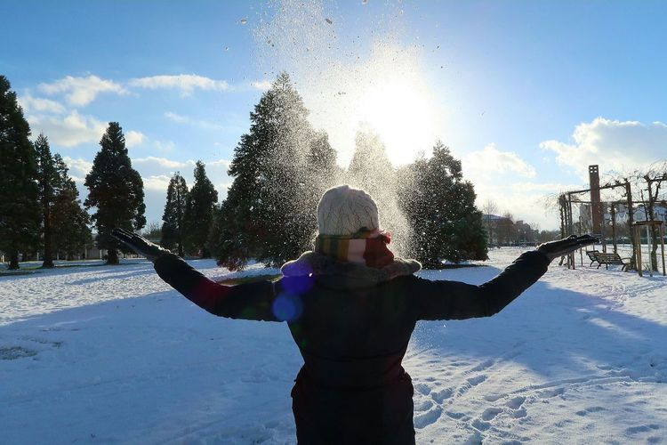 Woman standing on snow covered landscape against sky