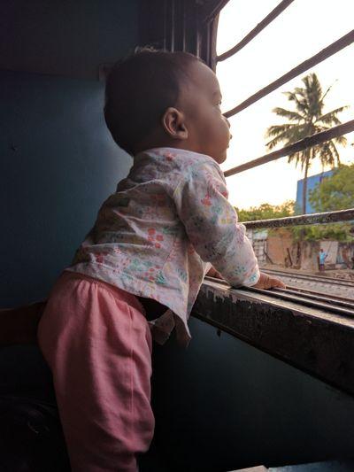 Cute baby girl looking through train window