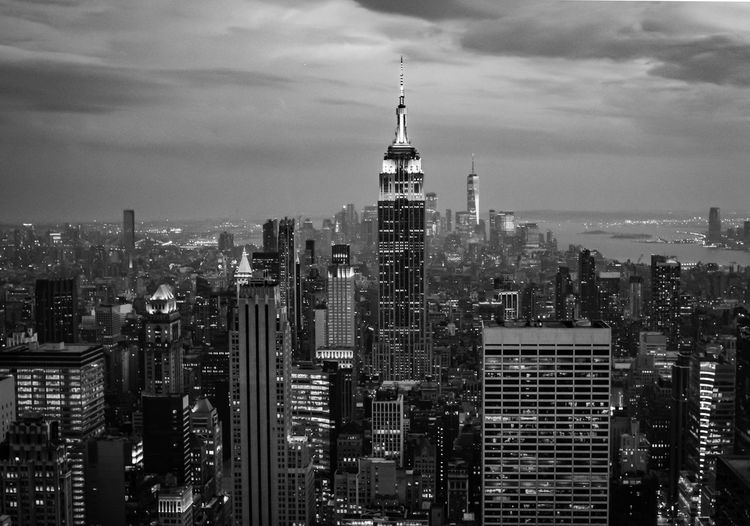 Aerial view of manhattan buildings in city against cloudy sky in black and white