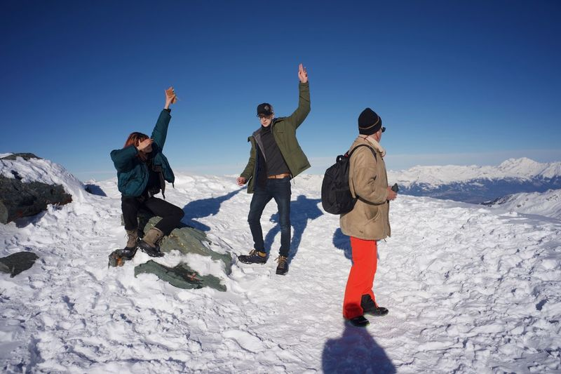 Friends enjoying on snow covered mountain against clear sky