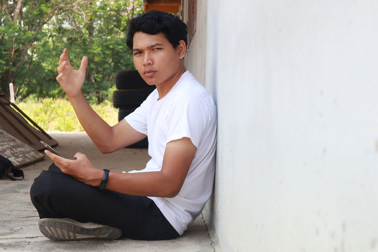 Side view of young man using mobile phone while sitting on wall