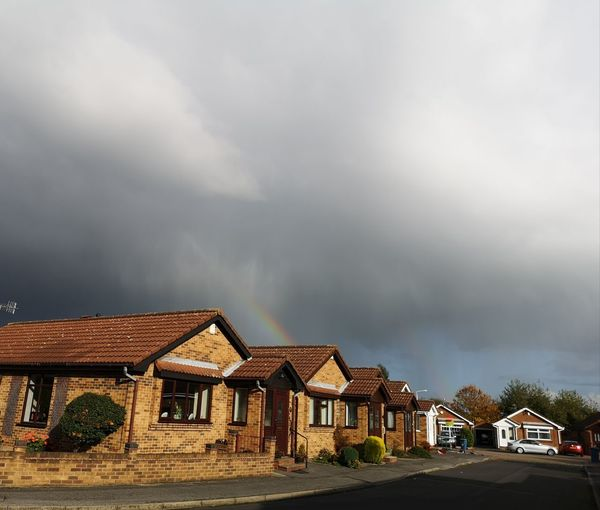 Houses by road against sky