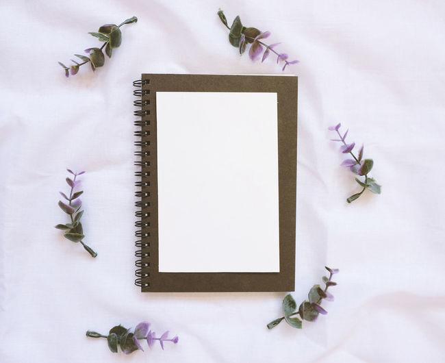 Directly above shot of spiral notebook with artificial flowers on fabric