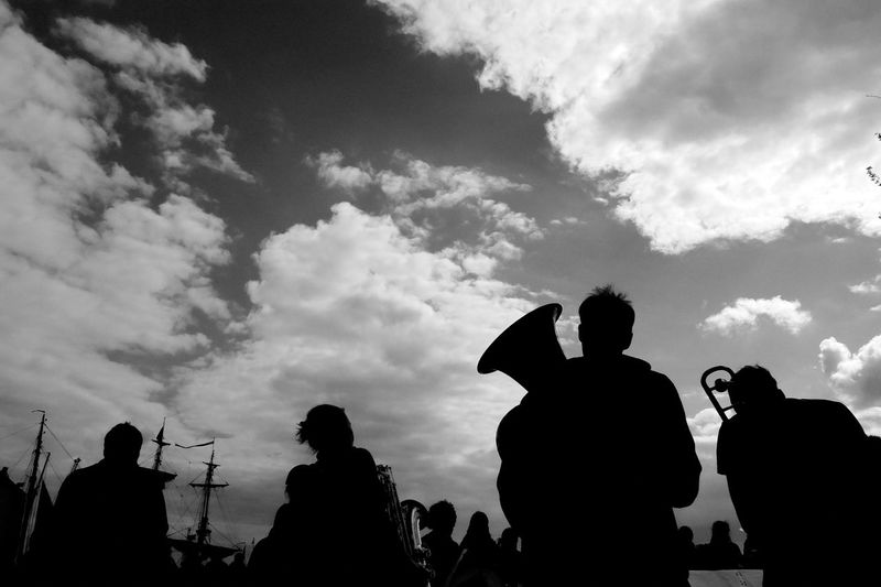 Silhouette people at music concert against sky