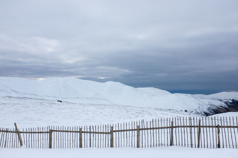 Scenic view of snow covered field against cloudy sky