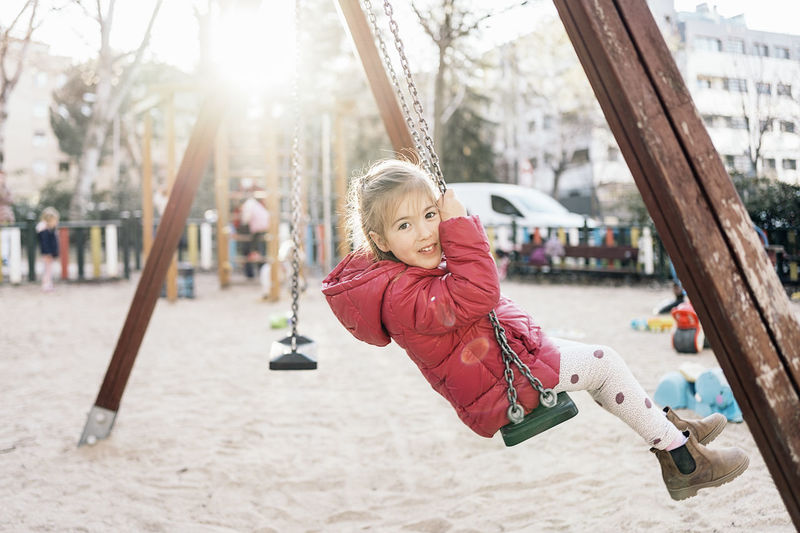 Cute girl playing with swing in playground