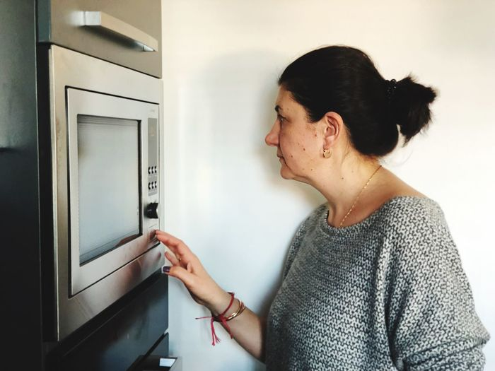 Side View Of Mature Woman Standing By Microwave At Home