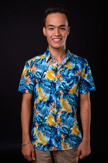 Portrait of smiling young man against black background