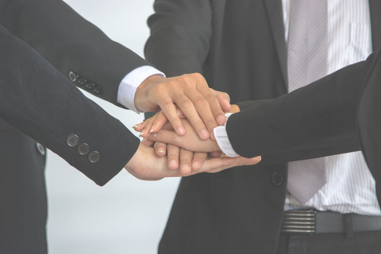 Midsection of colleagues stacking hands in office