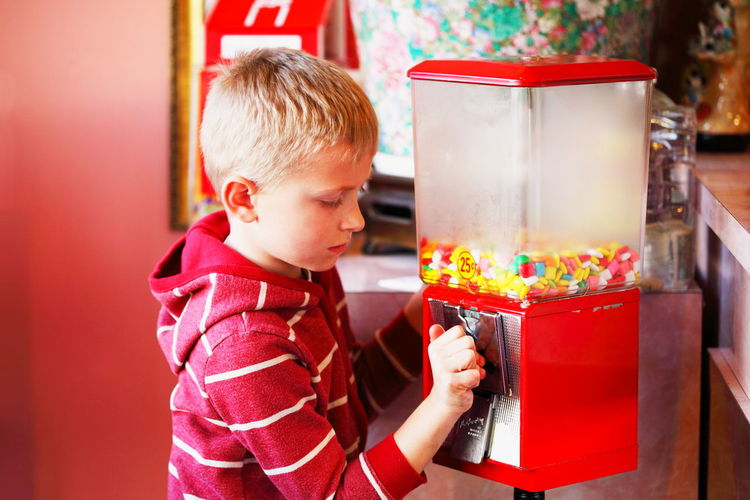 Boy playing with bubble gum machine