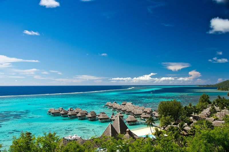 Scenic View Of Stilt Houses In Sea At Moorea Against Sky