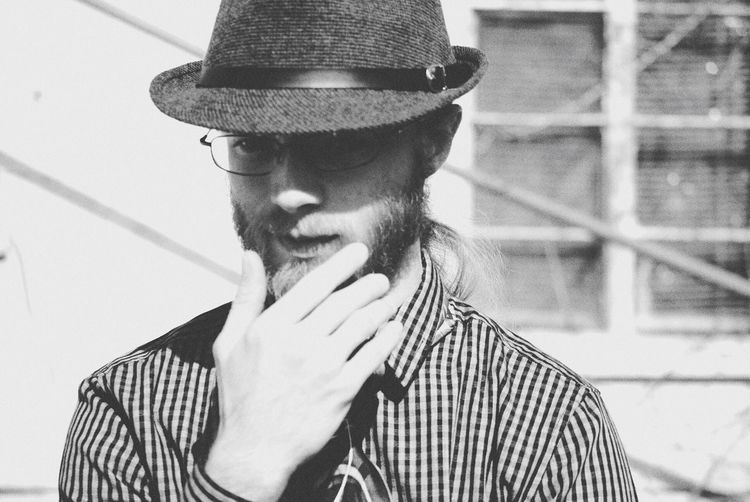 Bearded young man with hand on chin wearing hat during sunny day