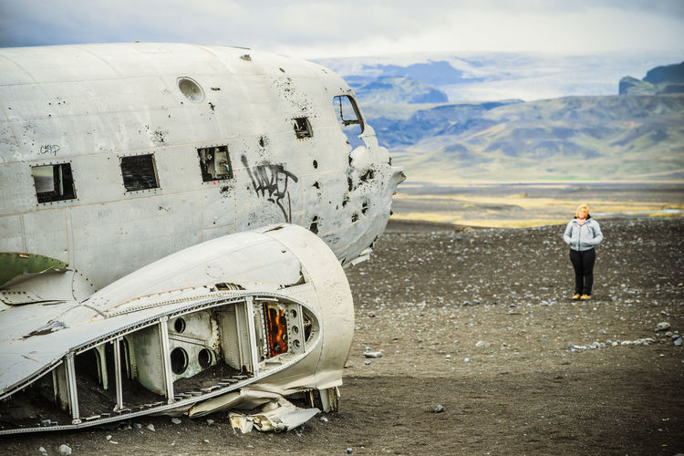 Full length of woman standing by abandoned airplane on sand