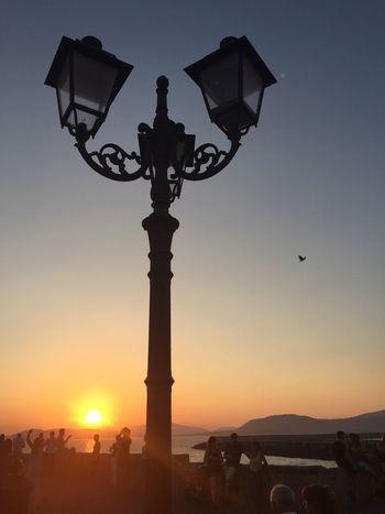 Sunset Dusk Sardinia By The Sea Sea Lantern Lamp Post Street Light Holiday Beautiful Sky Sun Down Sunset Over Sea Orange Sun Learn & Shoot: After Dark Italy Scenery Landscape Alghero Bird In Flight Yellow Sun People Watching Sunset