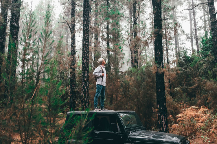 Man standing by car in forest