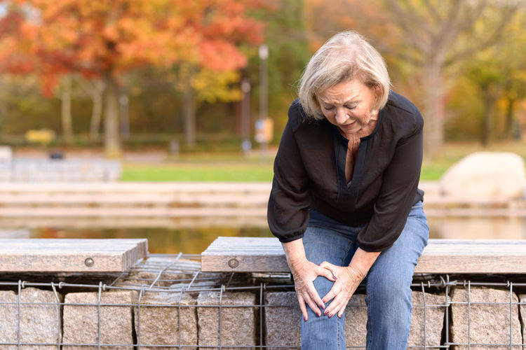 Woman holding knee while sitting at park